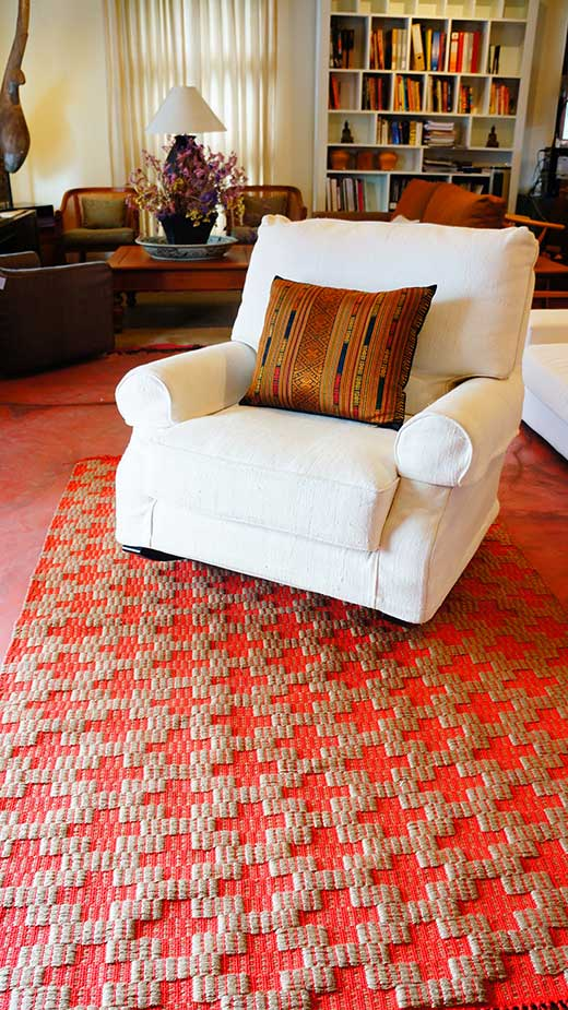 Armchair upholstered with thick handspun cotton; Lao brocade-woven silk pillow; twil-woven jute rug