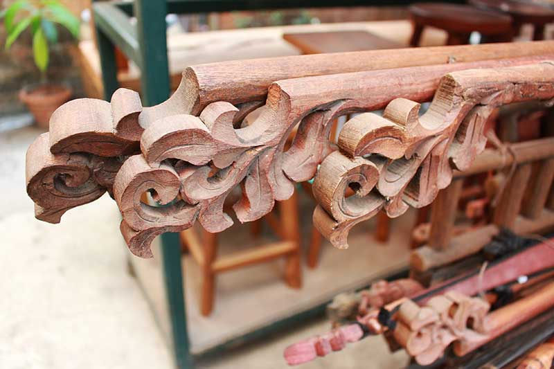 Traditional Thai Kanok-pattern carvings decorate the ends of fabric display hangers