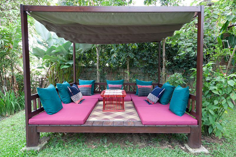 Multipurpose outdoor daybed features: retractable UV-proof sun shade; sedge (Krajude) woven floor mat; seat cushions and throw pillows covered in sturdy weather-resistant fabric.